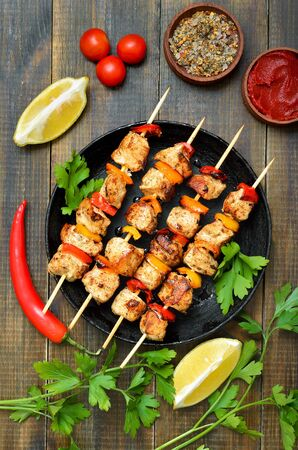 Barbecued chicken kebab with bell pepper in frying pan, vegetables and herbs on wooden table, top view Stock Photo