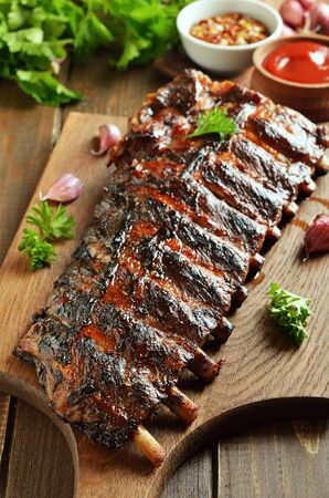 Spicy hot grilled spare ribs on cutting board, close up