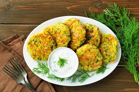 Vegetable cutlet from zucchini, carrot, herbs on wooden table. Healthy food. Top view, flat lay