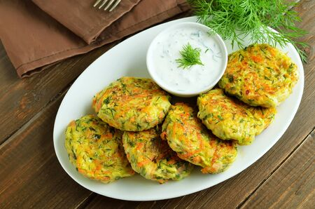 Vegetable cutlet from zucchini, carrot, herbs on wooden table