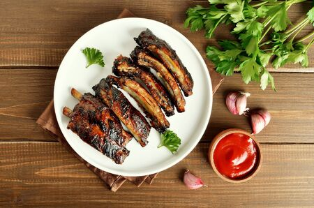 Grilled pork ribs on white plate. Tasty bbq meat. Top view, flat lay Banco de Imagens