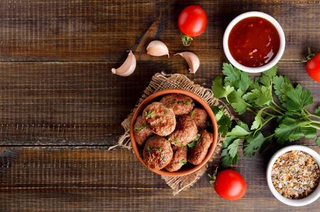 Homemade cutlets from minced meat in bowl and spices on wooden table. Top view, flat lay