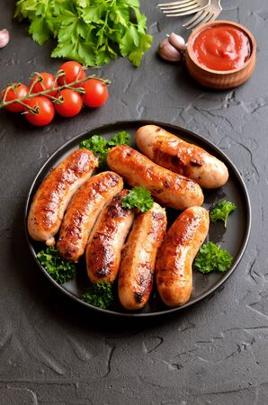 Fried sausage with fresh parsley on plate, fresh tomatoes and ketchup on table