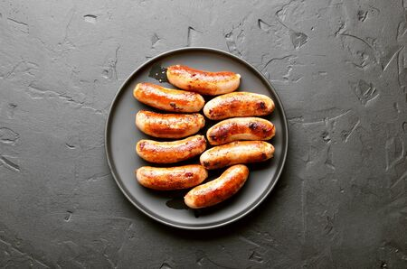 Fried sausage on over black stone background. Top view, flat lay Stock Photo