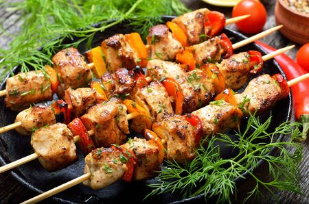 Fried chicken kebab with bell pepper in frying pan, close up view Foto de archivo