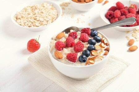Healthy breakfast. Oatmeal porridge with raspberries, blueberries and nuts in bowl on white table