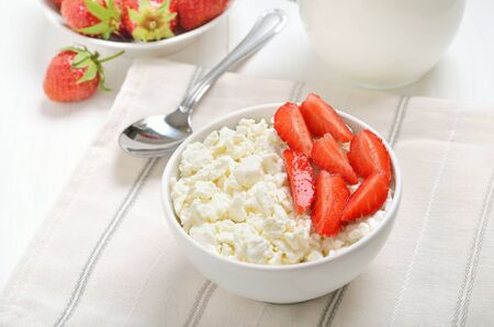 Curd cheese and strawberry in bowl on table. Healthy breakfast