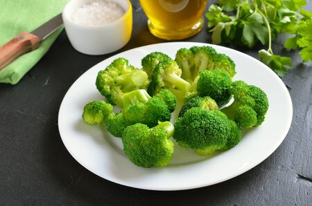 Vegetarian food. Broccoli on white plate on a dark surface