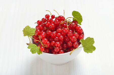 Fresh berries, red currants in bowl on  white table, vegetarian food