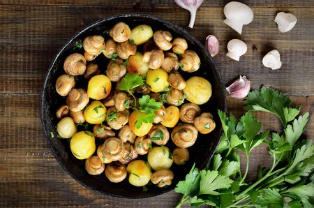 Fried mushrooms and potatoes in cast iron pan on wooden background. Top view, flat lay