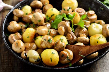 Fried mushrooms and potatoes in cast iron pan, close up view