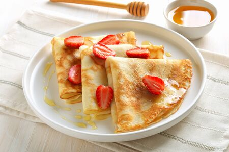 Crepes with strawberry slices, tasty breakfast, close up