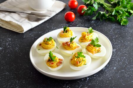 Deviled stuffed eggs with egg yolk, bacon, mustard and parsley on dark stone background Stock Photo