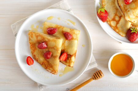 Homemade crepes with strawberry slices and honey, tasty breakfast. Top view, flat lay