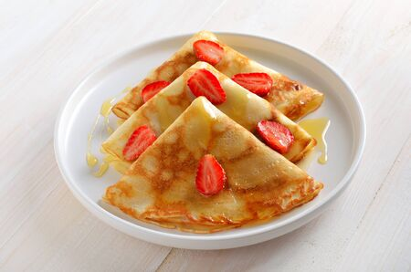Crepes with strawberry and honey on white plate, close up view. Appetizing breakfast