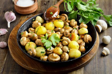 Delicious fried mushrooms with potatoes in cast iron pan on wooden background Stock Photo