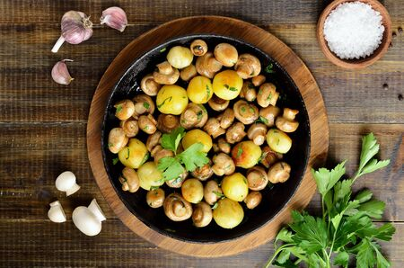 Delicious fried mushrooms with potatoes in cast iron pan on wooden background. Top view, flat lay Stock Photo
