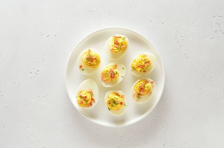 Deviled stuffed eggs with egg yolk, bacon, mustard and dill. Healthy diet food for breakfast. Top view, flat lay.