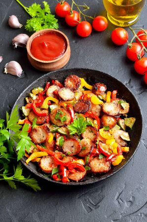 Grilled vegetables with sausages and herbs in frying pan, close up Stock Photo