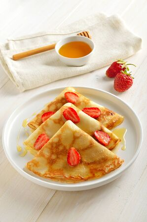 Crepes with strawberry and honey on white plate, breakfast