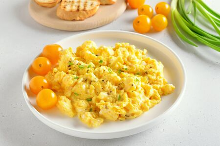 Scrambled eggs and tomatoes on plate over white stone background