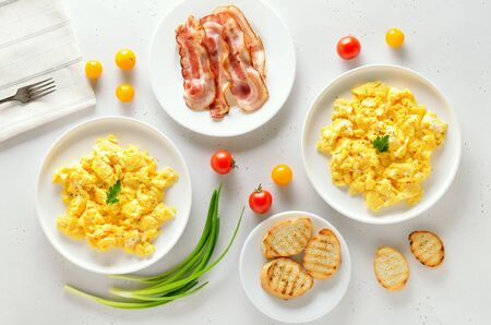 Healthy diet breakfast concept. Scrambled eggs, bacon and tomatoes over white stone background. Top view, flat lay