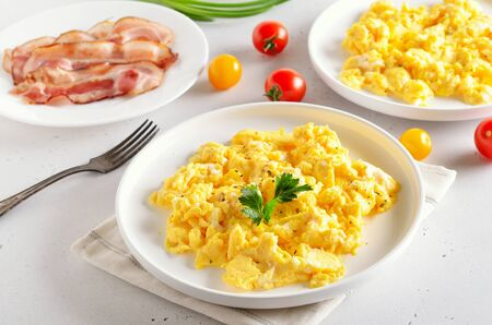 Healthy diet breakfast concept. Scrambled eggs, bacon and tomatoes over white stone background