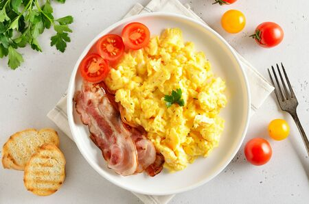 Scrambled eggs, fried bacon and tomatoes on plate over light stone background. Top view, flat lay