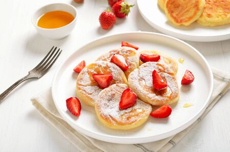 Homemade pancakes with cottage cheese and strawberry slices, healthy breakfast