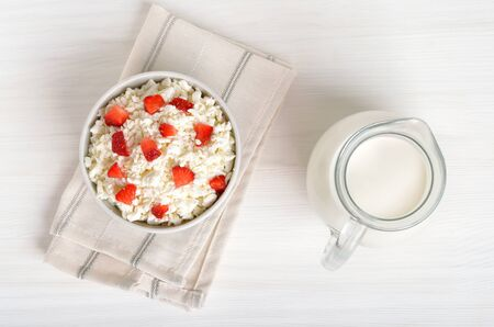 Curd cheese with strawberry slices in bowl and milk on table, top view. Healthy breakfast Stock Photo