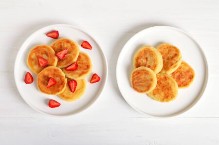Cottage cheese pancakes with strawberry, syrniki on white background. Traditional Russian breakfast. Top view, flat lay