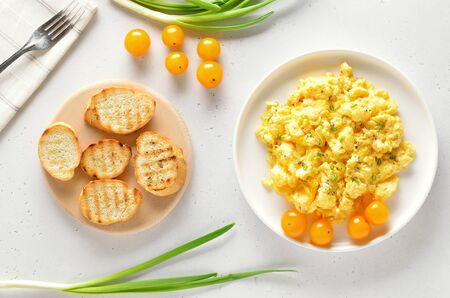 Scrambled eggs and tomatoes on plate over light stone background.  Top view, flat lay