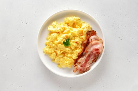 Scrambled eggs and fried bacon on plate over white stone background. Top view, flat lay