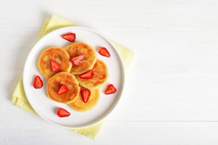 Cottage cheese pancakes with strawberry, syrniki on white background. Top view, flat lay