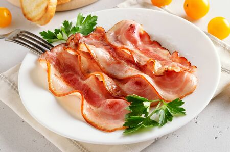 Fried bacon slices on plate over white stone background, close up view Stock Photo