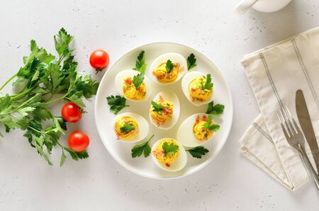 Stuffed eggs with egg yolk, bacon, mustard and parsley. Healthy diet food for breakfast. Top view, flat lay. Stock Photo