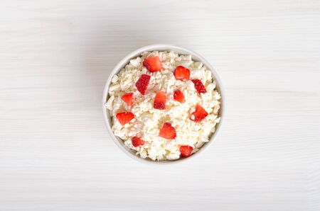 Curd cheese and strawberry in bowl on table, top view. Healthy breakfast Stock Photo