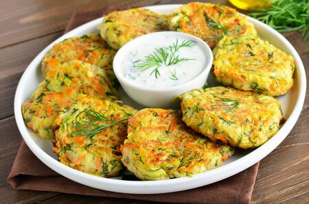 Diet vegetable cutlet from zucchini, carrot, herbs on wooden table
