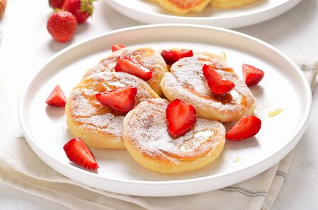 Homemade pancakes with cottage cheese and strawberry slices, healthy breakfast, close up view