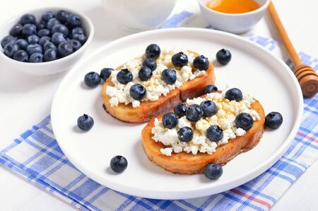 Sandwiches with curd cheese, blueberries and honey on white plate, close up view