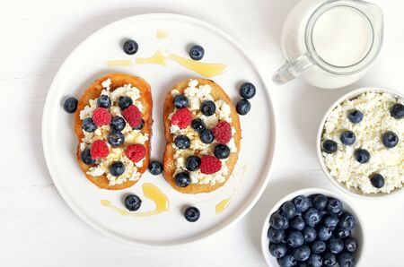 Sandwiches with curd cheese, blueberries, raspberries and honey on white plate. Fresh curd and blueberries in bowl. Top view, flat lay