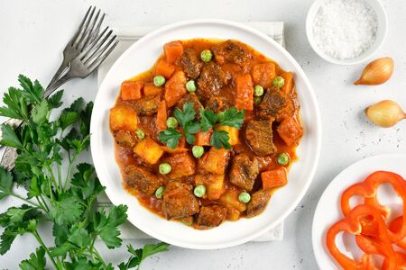 Beef stew with potatoes and carrots in tomato sauce on white stone Stock Photo