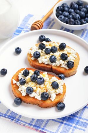 Sandwiches with curd cheese, blueberries and honey on white plate