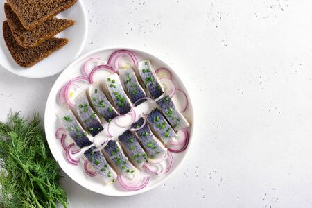 Salted herring with onion on plate on white stone