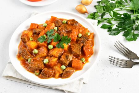 Beef stew with potatoes and carrots in tomato sauce on white plate Stock Photo - 144991864