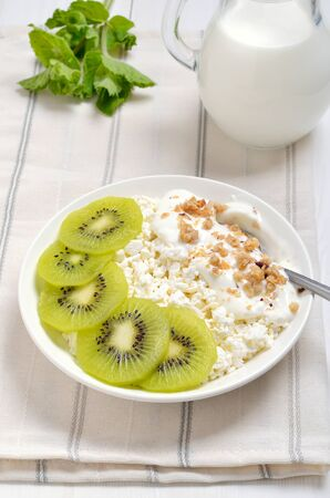 Cottage cheese with yogurt and kiwi slices. Healthy breakfast Stock Photo