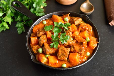 Beef stew with potatoes and carrots in tomato sauce in frying pan Stock Photo