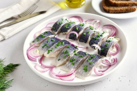 Salted herring with spice and onion on plate on white