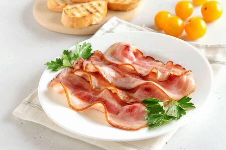 Fried bacon slices on plate over white stone background Stock Photo - 144995038