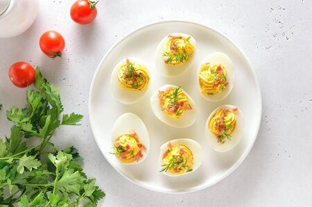Stuffed eggs with egg yolk, bacon, mustard and dill. Healthy diet food for breakfast. Top view, flat lay. Stock Photo - 144995153